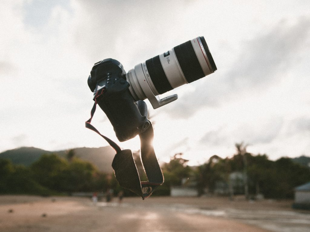 surrealism photo of white and black DSLR camera during golden hour